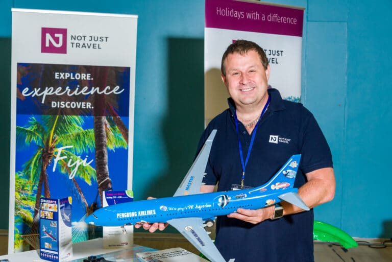 Photograph of Daniel Dobranski from Not Just Travel Leigh holding a replica aeroplane standing in front of his stand at Leigh Business Expo 2019