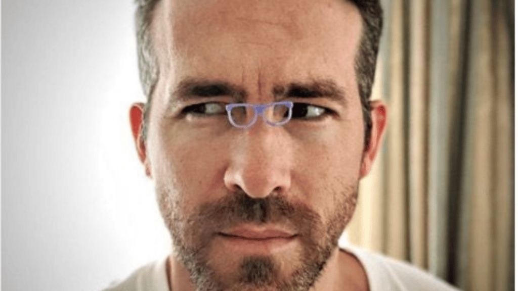 Photo of actor Ryan Reynolds wearing tiny glasses