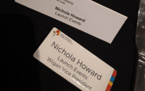 Image shows Nichola's Wigan Vice President of the Greater Manchester Chamber of commerce name badge on a table