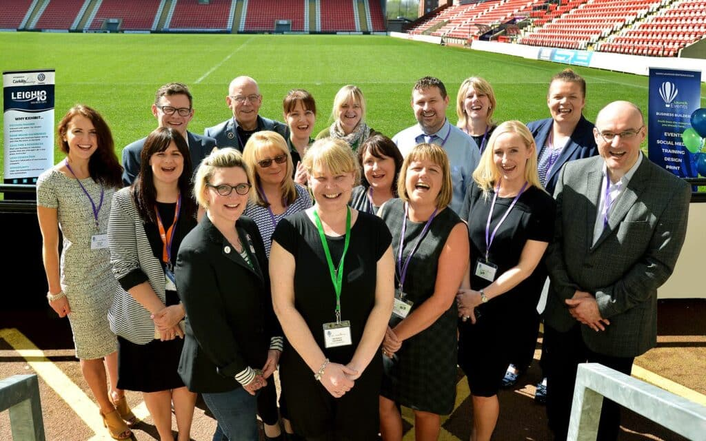 Photo of several local business men and women stood in front of Leigh centurions rugby pitch