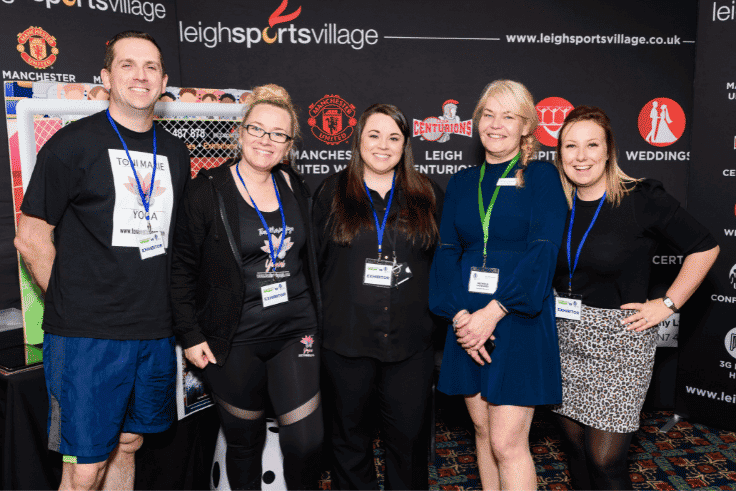 Photo of exhibitors from Toni Marie Yoga and Leigh Sports Village with Business Expo Wigan organiser Nichola Howard
